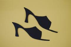 La carta ha tagliato delle scarpe delle donne sul fondo di abbronzatura Fotografia Stock