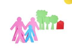 La carta ha tagliato i outs che rappresentano una famiglia con gli alberi ed alloggia sopra fondo bianco Fotografia Stock