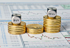 La carta, las monedas y los cubos financieros de los dados con las palabras venden la compra. Imagen de archivo libre de regalías