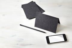 La carta nera ha piegato la cartolina, la matita, telefono cellulare sulla tavola di legno cancelleria Spazio per la disposizione Immagini Stock Libere da Diritti