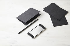 La carta nera ha piegato la cartolina, la matita, telefono cellulare sulla tavola di legno cancelleria Spazio per la disposizione Immagini Stock