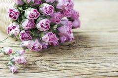 La carta rosa è aumentato nel canestro di tessuto su vecchio legno Fotografie Stock