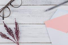 La carta rosa in bianco nel bianco avvolge, occhiali e penna nera Immagini Stock