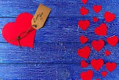 La carta rossa del cuore ha tagliato su fondo di legno blu Fotografia Stock