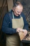 La carta vetrata degli uomini frantuma i prodotti del legno in un'officina immagine stock