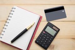 La carta vuota del taccuino, del calcolatore, della penna e del cradit di vista superiore ha messo sopra il wo Immagini Stock