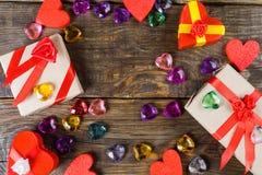 La cartapesta dei contenitori di regalo sotto forma di cuori rossi legati con i nastri ed i regali del raso ha imballato dalla ca Immagine Stock Libera da Diritti