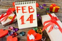 La cartapesta dei contenitori di regalo sotto forma di cuori rossi legati con i nastri ed i regali del raso ha imballato dalla ca Immagini Stock