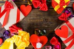 La cartapesta dei contenitori di regalo sotto forma di cuori rossi legati con i nastri ed i regali del raso ha imballato dalla ca Fotografie Stock Libere da Diritti