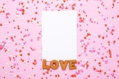 La carte actuelle avec des biscuits de lettres aiment et dentellent, les coeurs rouges sur le fond rose image libre de droits
