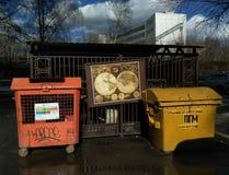 La carte antique de puzzle d'image du monde accroche dans le décharge de ville entre deux conteneurs de déchets photos stock