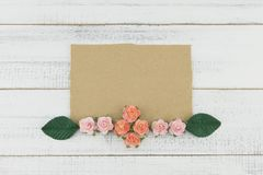 La carte brune vierge décorent des fleurs de papier de rose de rose et des feuilles de vert Images stock