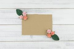 La carte brune vierge décorent des fleurs de papier de rose de rose et des feuilles de vert Photographie stock libre de droits