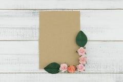 La carte brune vierge décorent des fleurs de papier de rose de rose et des feuilles de vert Photographie stock