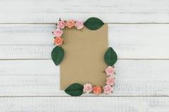 La carte brune vierge décorent des fleurs de papier de rose de rose et des feuilles de vert Photo libre de droits