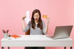 La carte de crédit criarde de flèche de chute de valeur de maintien de femme frustrante se reposent et fonctionnent au bureau bla photo libre de droits