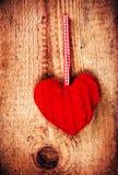 La carte de jour de valentines avec le coeur rouge sur le vintage en bois a donné à b une consistance rugueuse Photos stock