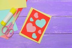 La carte de jour de valentines avec des coeurs, scissirs, bâton de colle, papier coloré couvre sur un fond en bois avec l'espace  Image stock
