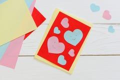 La carte de jour de valentines avec les coeurs roses et bleus, ciseaux, bâton de colle, papier coloré couvre sur un fond en bois  Photographie stock libre de droits