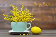 La carte de Pâques heureuse avec l'oeuf et le ressort de pâques fleurit dans la tasse Image stock