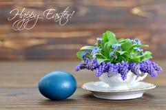 La carte de Pâques heureuse avec l'oeuf et le ressort de pâques fleurit dans la tasse de thé Photo stock
