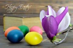 La carte de Pâques heureuse avec les oeufs et la magnolia de pâques fleurit Photographie stock