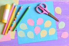 La carte de papier avec des ballons à air, ciseaux, bâton de colle, ballons à air de papier, papier coloré, crayonne sur une tabl Photographie stock libre de droits