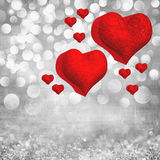 La carte de Saint-Valentin avec deux coeurs rouges en métal 3D allument le fond Images libres de droits