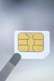 La carte de Sim pour le téléphone portable intelligent avec la brucelles, se ferment  Image libre de droits