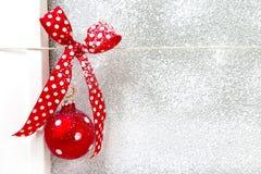 La carte de voeux avec un rouge a pointillé le ruban sur un fond blanc Photographie stock