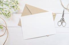La carte de voeux blanche vierge avec le brun enveloppent photo stock