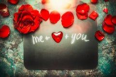 La carte de voeux de jour de valentines avec les roses rouges, bokeh, coeur et textotent vous et moi, vue supérieure composant Am Photo stock
