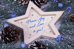 La carte de voeux de vacances de nouvelle année de Noël de Noël avec la paix en bois de cinq d'étoile de sapin de branches de côn Image stock