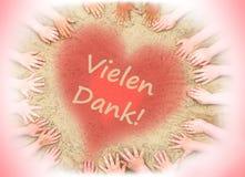 La carte de voeux des mains des enfants et un coeur avec les mots allemands vous remercient photo stock