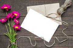 La carte de voeux et l'enveloppe blanches vides avec la camomille rose fleurit le bouquet Images stock