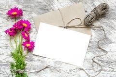 La carte de voeux et l'enveloppe blanches vides avec la camomille rose fleurit le bouquet Image libre de droits