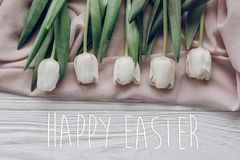 La carte de voeux heureuse des textes de Pâques se connectent les tulipes blanches élégantes dessus Photos libres de droits