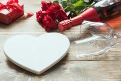 La carte de voeux de jour de valentines avec la rose de rouge de bouquet fleurit, une bouteille de champagne, coeur comme blanc e Images stock