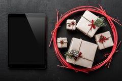 La carte de voeux de Noël, hors des cadeaux de nouvelle année, envoient alors un message de salutation à votre cher ipad, fond po Images stock