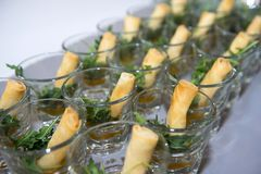 A la carte designed crispy deep-fried spring roll with rucola in. Mini glass serve for snack time stock photos