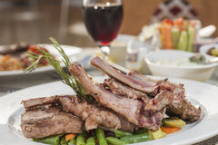 A la carte lamb chop meal on patterned plate. Closeup detail of an a la carte lamb chop meal in restaurant on patterned plate royalty free stock images