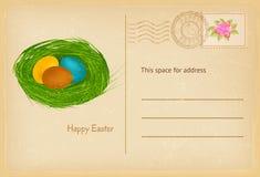 La carte postale de Pâques dans le style de vintage avec des oeufs de pâques et l'herbe nichent la carte de voeux heureuse de cél Photographie stock