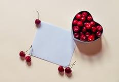 La carte pour des notes et les cerises au coeur forment le boîte-cadeau Photos stock