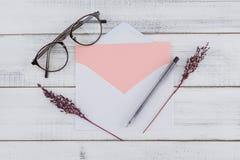 La carte rose vierge dans le blanc enveloppent, des lunettes image libre de droits
