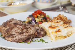A la carte steak meal on patterned plate. Closeup detail of an a la carte steak meal in restaurant on patterned plate royalty free stock photos