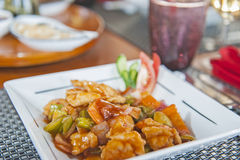 A la carte sweet and sour meal on patterned plate. Closeup detail of an a la carte chinese sweet and sour chicken meal in restaurant on patterned plate stock image