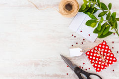 La carte vide attachée sur le rouge a pointillé le boîte-cadeau au-dessus du fond en bois blanc Copiez l'espace Paillettes en for Image libre de droits