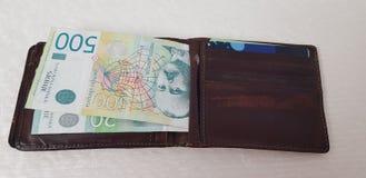 La cartera con las tarjetas de crédito y los billetes serbios ponen en la tabla blanca fotos de archivo libres de regalías