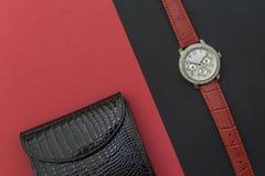 La cartera de cuero laqueada de las mujeres negras y el reloj de las mujeres en fondos negros y rojos Reloj con los cristales fotos de archivo