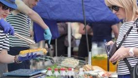 La cartera en manos del comprador en el mercado, vendedor sostiene los alimentos de preparación rápida, pago en la comida basura, almacen de metraje de vídeo
